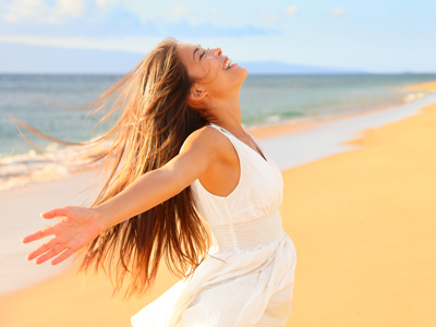 浜辺で両手を広げる女性