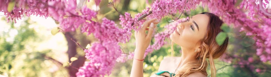 ピンクの花に顔を近づける女性